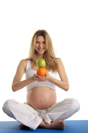 Pregnant woman practicing yoga and keeps fruit Stock Photo - 9715337