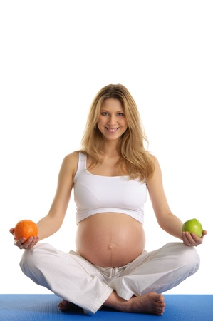Pregnant woman practicing yoga and keeps fruit Stock Photo - 9715347