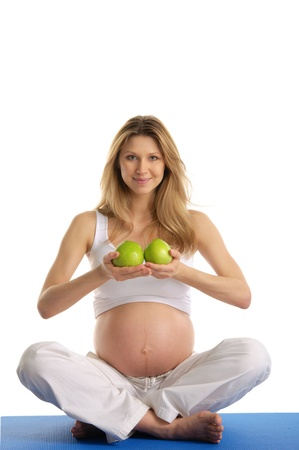 Pregnant woman practicing yoga and keeps apples Stock Photo - 9715346