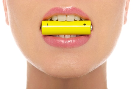 Woman holding battery in his mouth