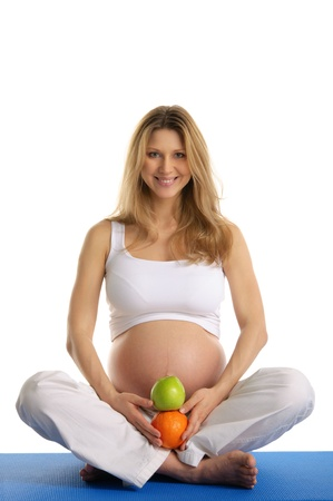 Pregnant woman practicing yoga and keeps fruit Stock Photo - 9869906