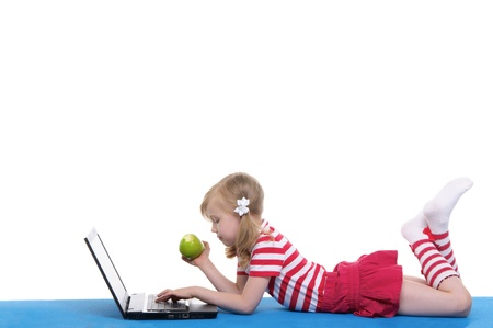 girl with an apple and laptop on rug photo