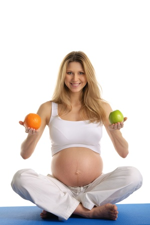 Pregnant woman practicing yoga and keeps fruit Stock Photo - 9870423