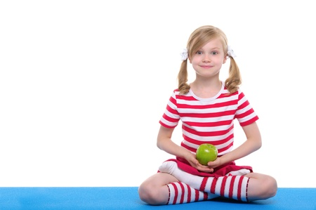 girl with open eyes practice yoga and keep apple Standard-Bild
