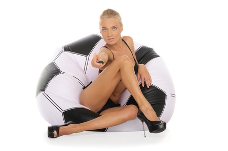 Woman with remote control in chair of soccer ball photo