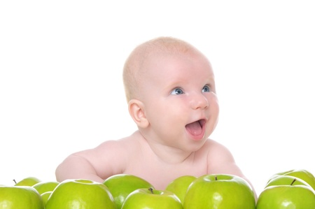 pleasantness: small child sitting in the green apples Stock Photo