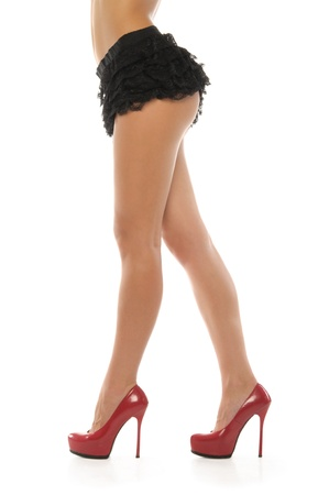 Beautiful female legs in red shoes and skirt photo