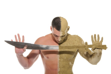 young man half smeared with clay with sword\ Stock Photo - 10634255