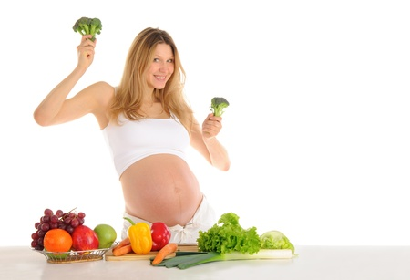 pleasantness: Dancing pregnant woman with fruits and vegetables isolated on white