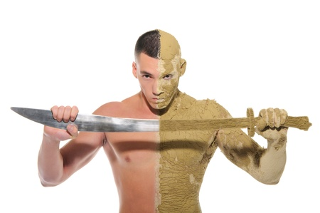 tension: young man half smeared with clay with sword isolated on white Stock Photo