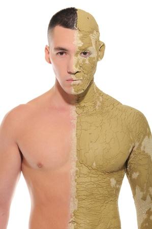 若い男が半分白で隔離される粘土にまみれて