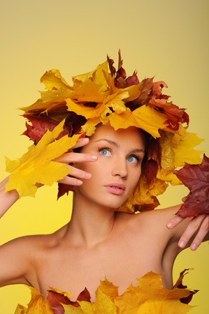 Beautiful woman with autumn leaves on yellow photo