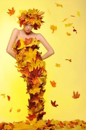 葉と落葉のドレスを着た女性