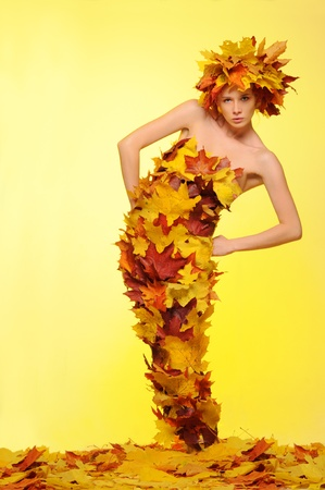 woman in gown of autumn leaves Stock Photo