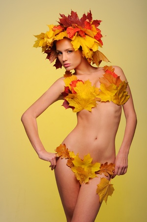 Beautiful woman in lingerie of autumn leaves