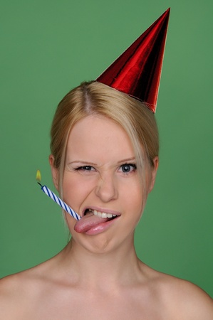 adult birthday: woman with candle in tongue and festive cap