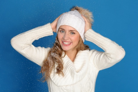 happy woman in winter clothes under falling snow photo