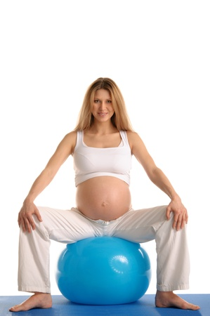 pleasantness: pregnant woman practicing yoga with blue ball isolated on white