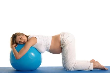 妊娠中の女性を白で隔離される青いボールと一緒にヨガを練習 写真素材