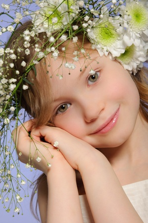 Vertical portrait of girl with wreath of flowers on blue background photo
