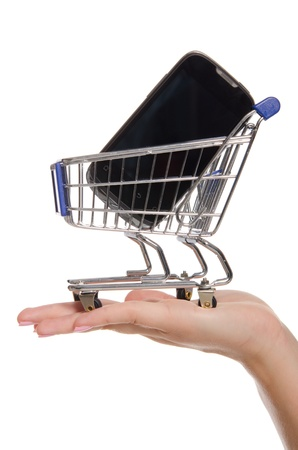 mobile shopping: smartphone in shopping trolley on the palm