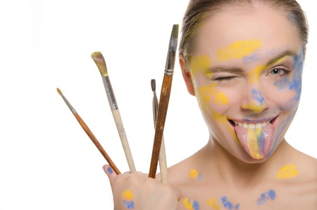 pleasantness: woman with brushes and  paint on face shows tongue Stock Photo