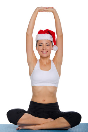 Asian girl doing yoga in a cap of Santa Claus