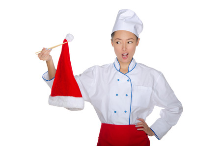 Chef holding chopsticks Christmas cap isolated on white photo