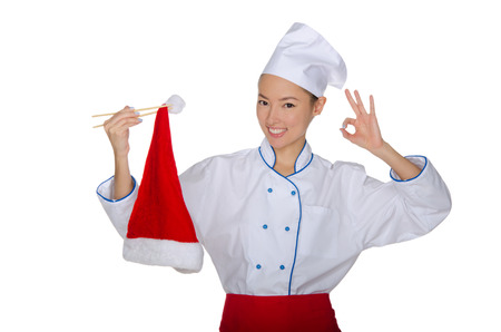 Chef holding chopsticks cap of Santa Claus isolated on white photo