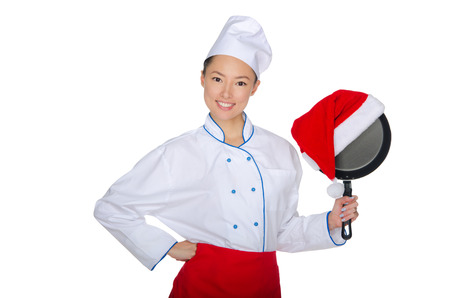 Asian chef and a frying pan in Santa hat isolated on white photo