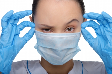 Young doctor wearing a mask and gloves isolated on white photo