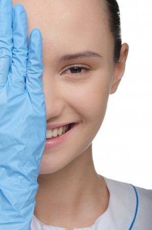 Smiling doctor with blue surgical gloves and white uniform photo