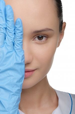 Face of a young woman partially covered with gloved hands photo