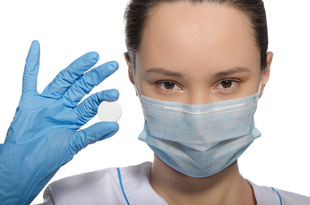 Doctor in gloves holds pill isolated on white photo
