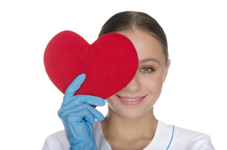 Smiling woman doctor right eye covered with red heart symbol photo