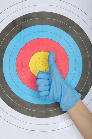 experimenter: Hand in glove on background of multicolored target Stock Photo