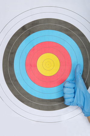 experimenter: Ok gesture in blue glove on a background of colored target