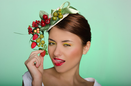 Young woman in elegant hat stuck out her tongue