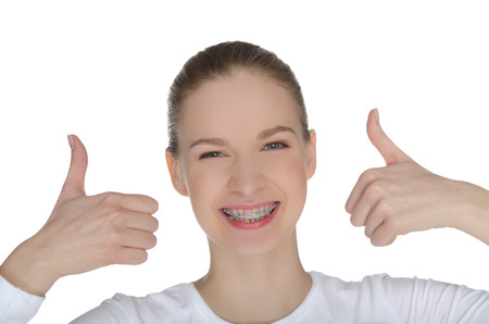 white backing: Smiling happy girl with braces isolated on white