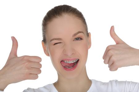 Glimlachend gelukkig meisje met beugels op de tanden op wit wordt geïsoleerd