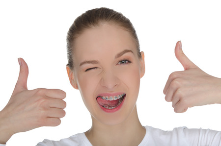 pleasantness: Smiling happy girl with braces on teeth  isolated on white