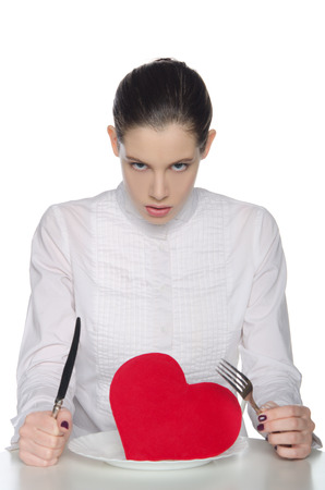 femme fatale: Femme fatale in white blouse eats heart knife and fork