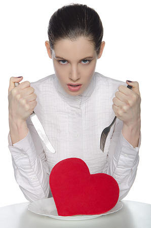 Femme fatale in white blouse threatening heart on a plate photo