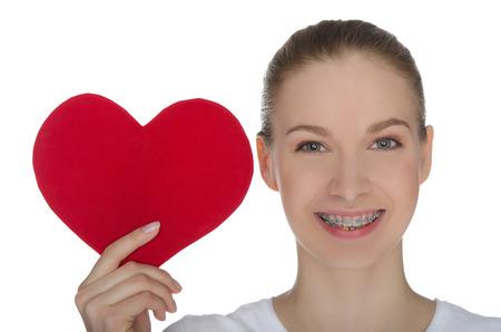 Gelukkig meisje met steunen op tanden en rood hart op wit wordt geïsoleerd
