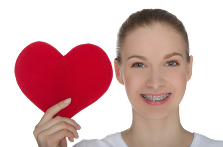 Happy girl with braces on teeth and red heart isolated on white photo