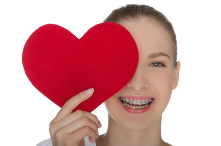Happy girl with braces on teeth and heart isolated on white photo
