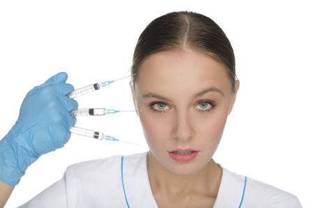 Doctor in gloves holding the syringe in his hand in front of their face photo