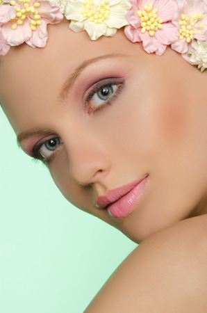 face make up: Portrait of a woman with white and pink flowers in her hair