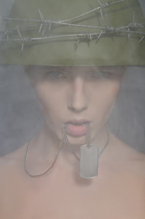 conscription: Portrait of woman in army helmet with a coin in his mouth Stock Photo