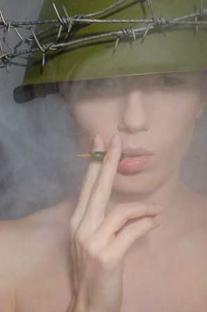 conscription: Portrait of woman in fog with a helmet and  cigarette-bullet